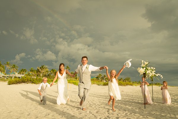 happy wedding couple run on beach with children with rainbow in sky