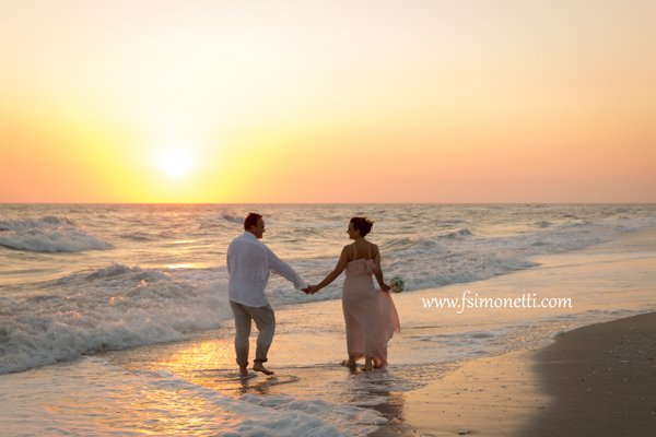 bride and groom walk along Sanibel beach at sunset