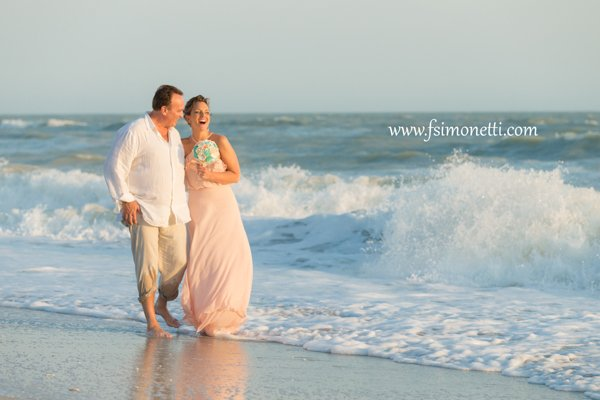 wedding couple walk along Sanibel beach after ceremony