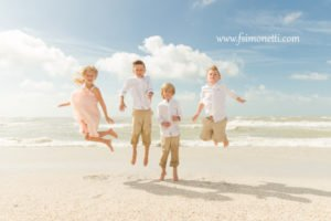 children jump on beach at parents' vow renewal ceremony