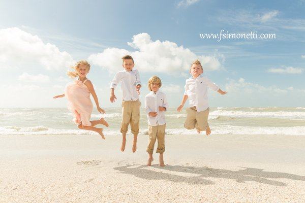 children jump on beach at parents wedding