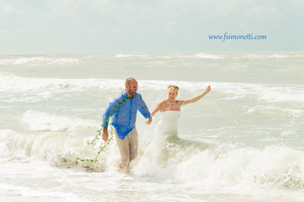 couple have fun in the ocean after their vow renewal ceremony