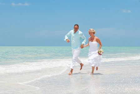 photograph of bride and groom running on the beach at their sanibel island destination wedding