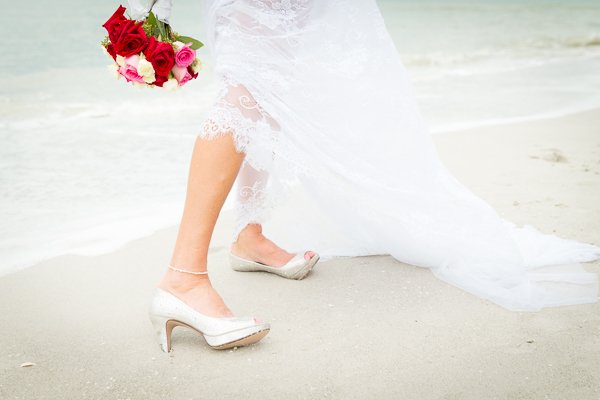 bride shows her shoes and flowers in beach sand