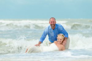 husband and wife enjoy waves during photo session