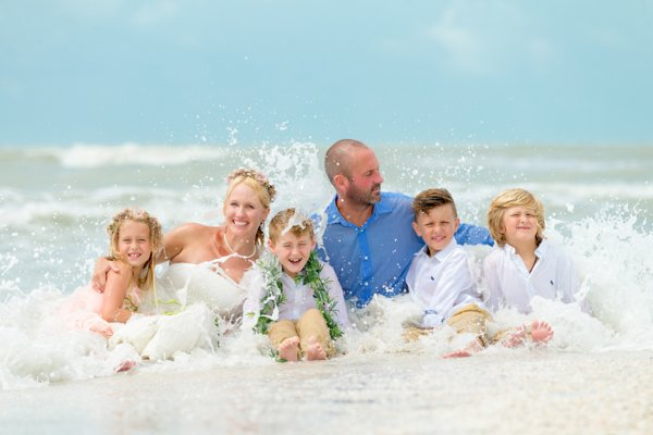 family enjoys photo in the ocean with waves