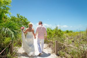bride and groom walk to Sanibel beach