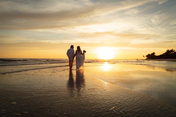 wedding couple walk on beach at sunset