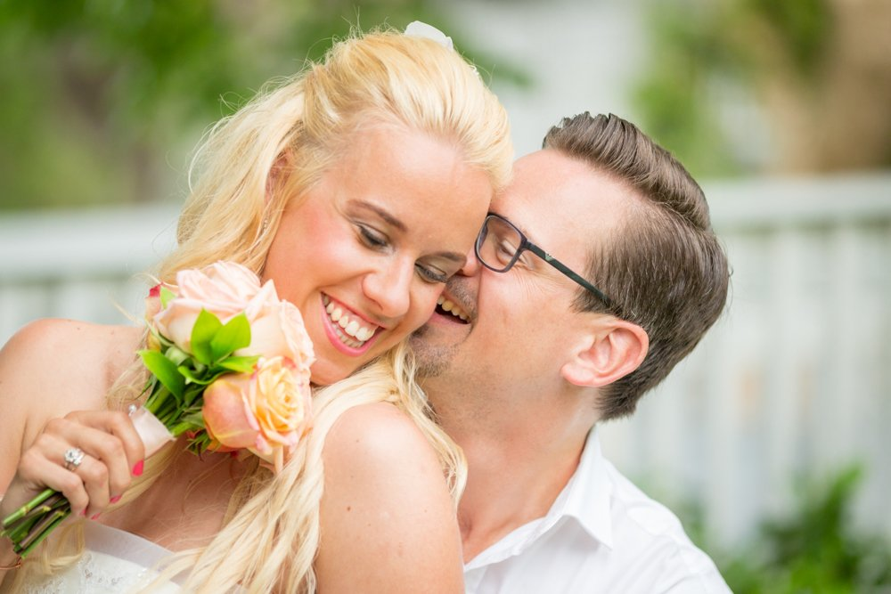 bride and groom kiss after beach wedding