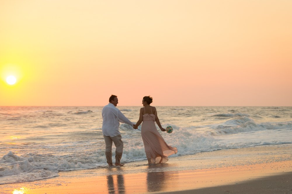 wedding couple walk along Sanibel beach at sunset