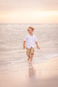 little boy runs on beach at parent's vow renewal ceremony