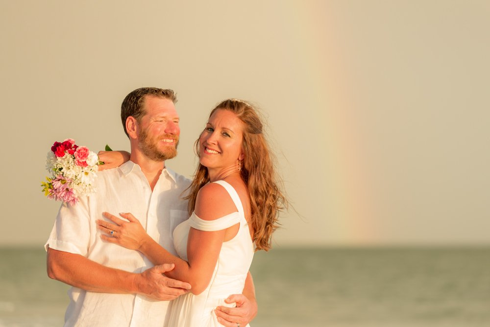 wedding couple with rainbow in background