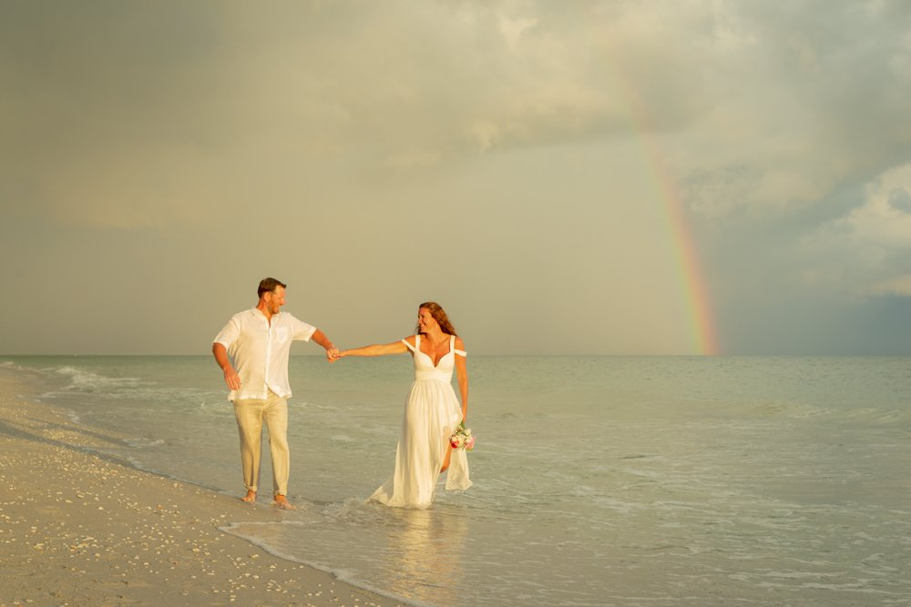 wedding couple enjoy a rainbow over their wedding ceremony