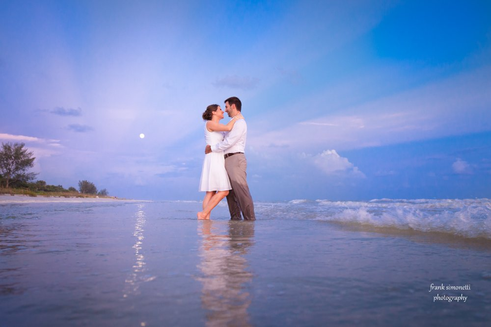 bride and groom stand on beach with moon in background