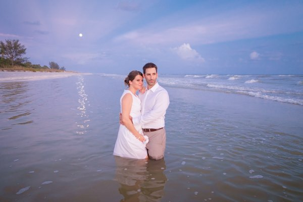 wedidng couple stand in ocean with moon in background