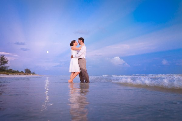 wedding couple stand in ocean with moon in background