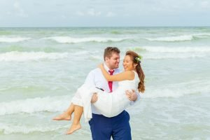 groom carries bride across waves in ocean