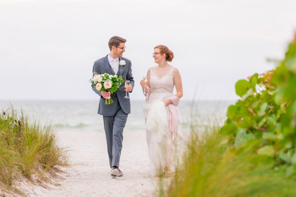 bride and groom walk along Sanibel beach